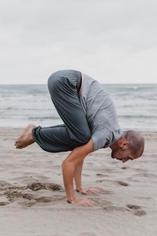 Zijaanzicht van de mens die yogaposities op het strand beoefent