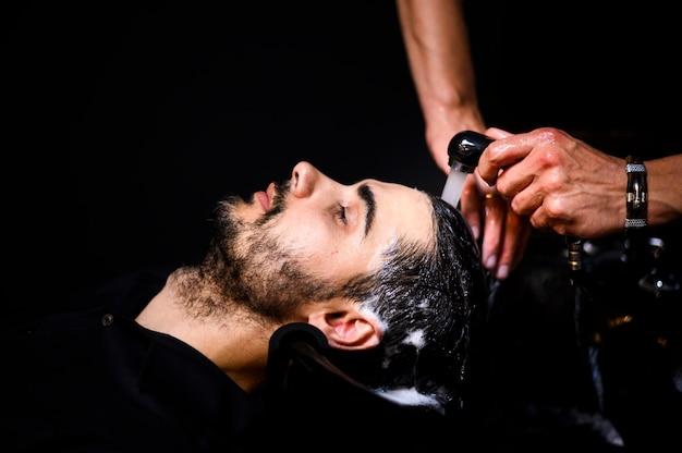 Zijaanzicht van de mens die zijn haar heeft dat bij salon wordt gewassen