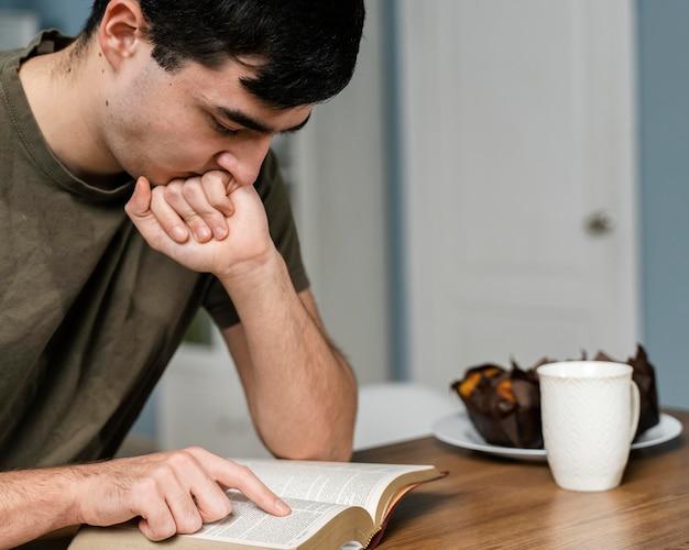 Zijaanzicht van de mens in de keuken die uit de bijbel leest
