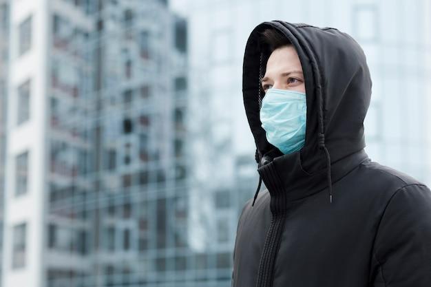 Zijaanzicht van de mens in de stad die medisch masker draagt