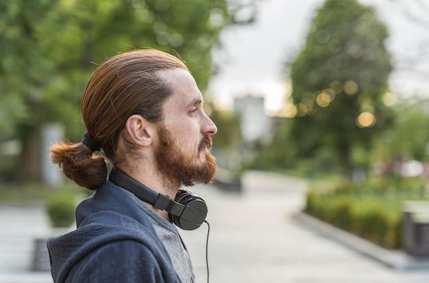 Zijaanzicht van de mens in de stad met een koptelefoon