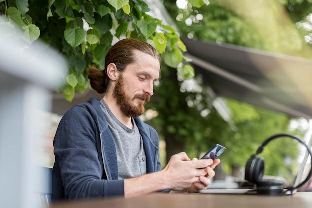 Zijaanzicht van de mens in de stad met smartphone en koptelefoon