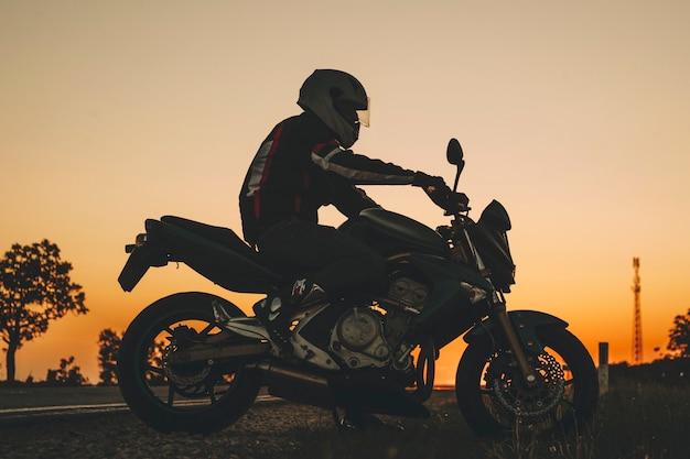 Zijaanzicht van de mens in helm rijden op donkere weg op motor bij zonsondergang op platteland