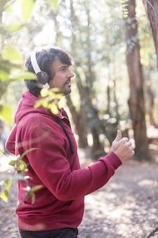 Zijaanzicht van de mens in hoodie het lopen in het park