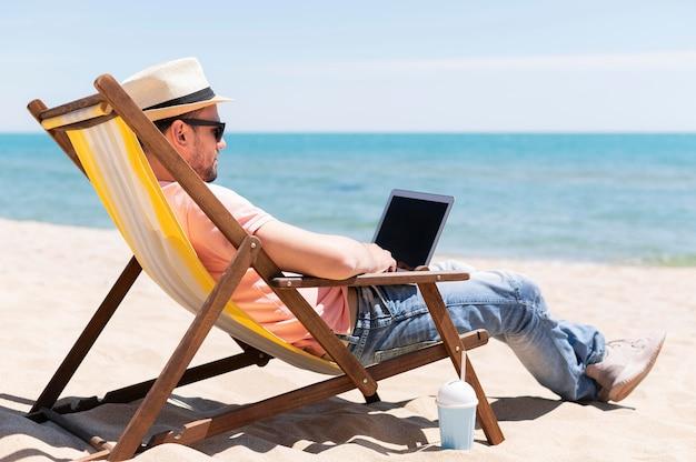 Zijaanzicht van de mens in strandstoel die aan laptop werkt