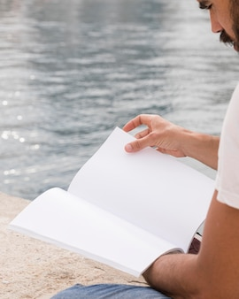 Zijaanzicht van de mens met boek aan het meer