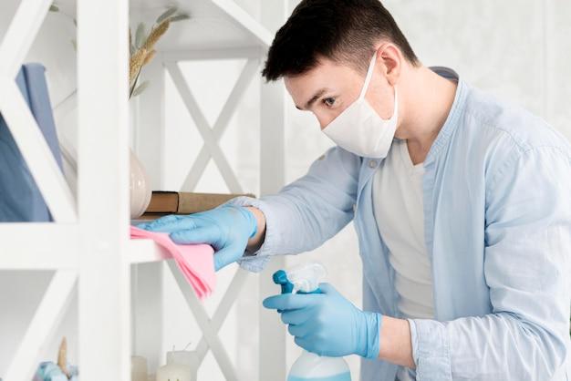 Zijaanzicht van de mens met gezichtsmasker het schoonmaken