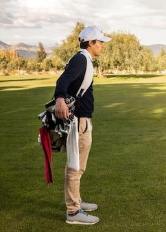 Zijaanzicht van de mens met golfclubs op het veld