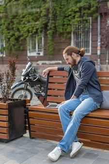 Zijaanzicht van de mens met laptop buiten in de stad