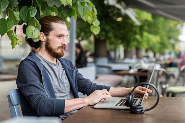 Zijaanzicht van de mens met laptop en hoofdtelefoon op stadsterras