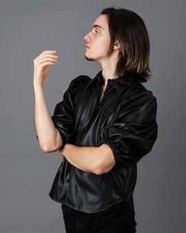 Zijaanzicht van de mens met make-up en leren jas