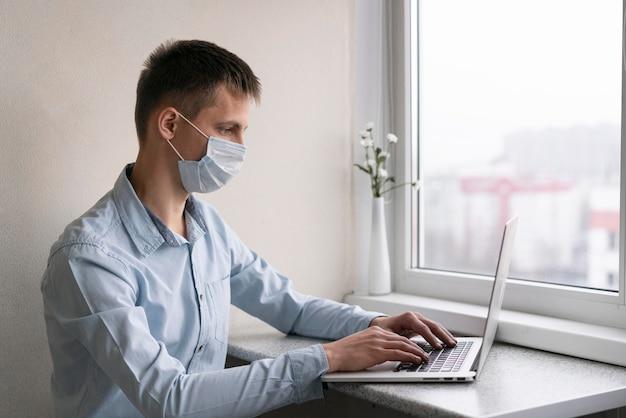 Zijaanzicht van de mens met medisch masker dat aan smartphone werkt