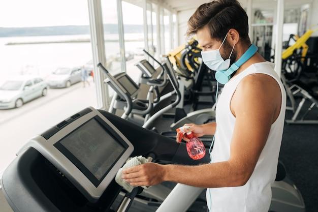 Zijaanzicht van de mens met medisch masker dat de loopband bij de gymnastiek desinfecteert