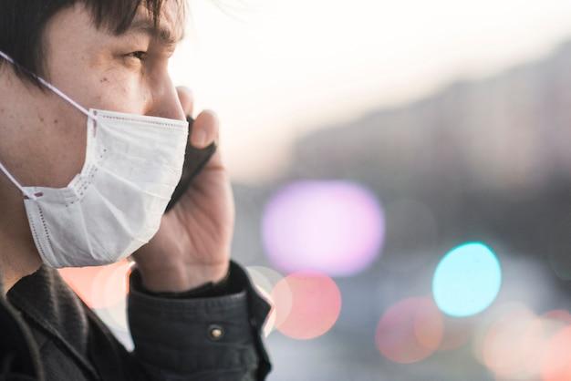 Zijaanzicht van de mens met medisch masker dat op de telefoon spreekt