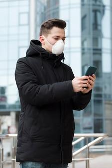 Zijaanzicht van de mens met medisch masker dat zijn telefoon in de stad bekijkt