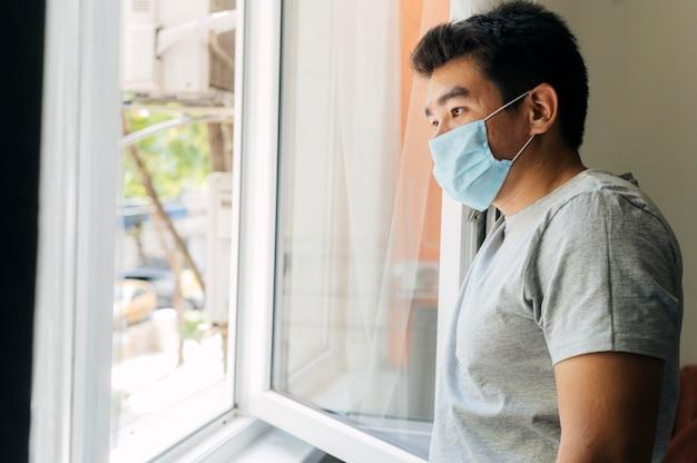 Zijaanzicht van de mens met medisch masker thuis tijdens de pandemie die door het venster kijkt