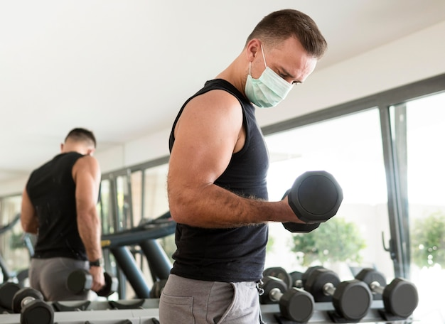 Zijaanzicht van de mens met medisch masker trainen in de sportschool