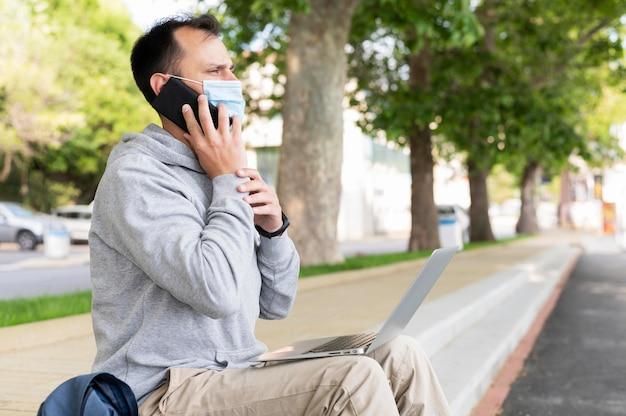Zijaanzicht van de mens met medische masker en laptop buitenshuis