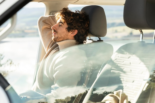 Zijaanzicht van de mens ontspannen in de auto tijdens een roadtrip