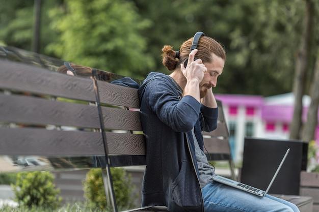Zijaanzicht van de mens op bankje in de stad met laptop