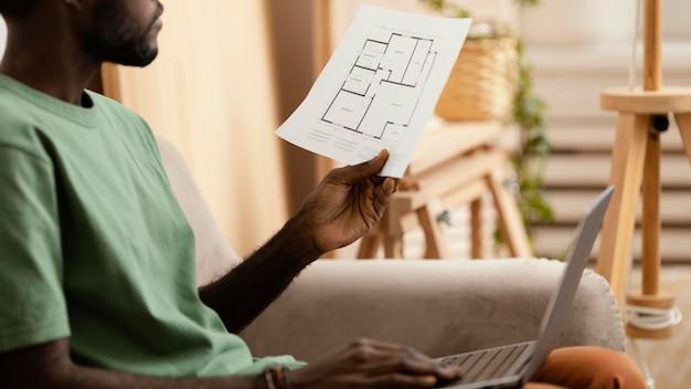 Zijaanzicht van de mens op de bank die een plan maakt om huis met laptop opnieuw in te richten