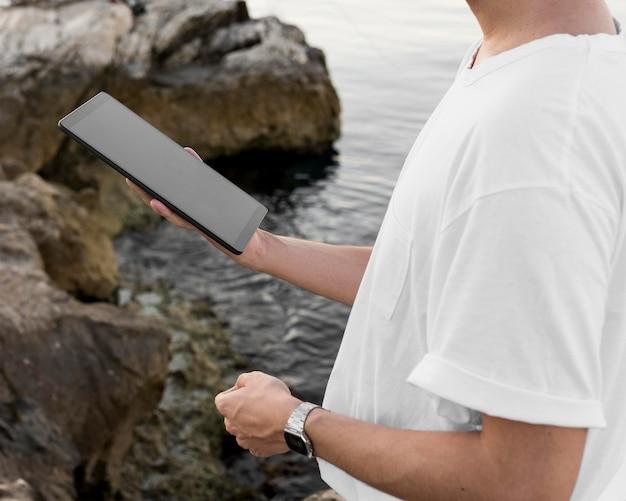 Zijaanzicht van de mens op de tablet van de strandholding