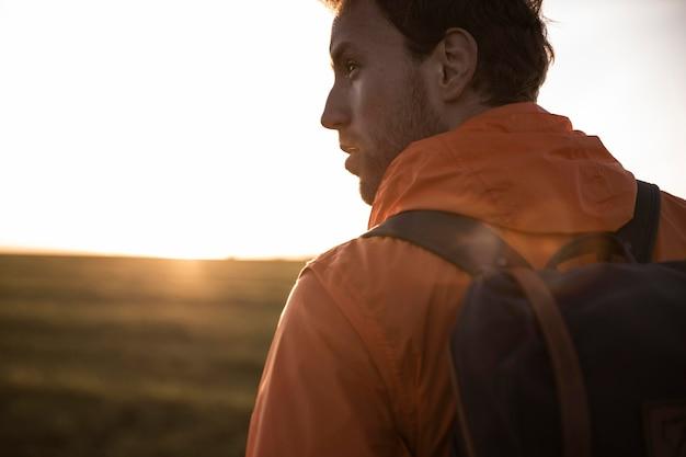 Zijaanzicht van de mens op een roadtrip in de zon die het uitzicht bewondert