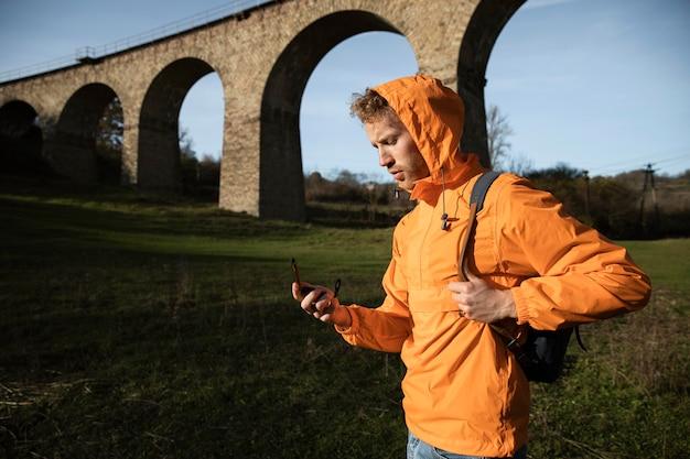 Zijaanzicht van de mens op een roadtrip poseren voor aquaduct terwijl hij kompas vasthoudt