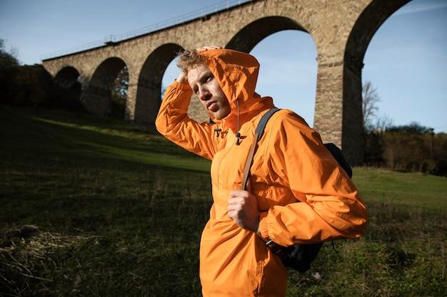 Zijaanzicht van de mens op een roadtrip poseren voor aquaduct