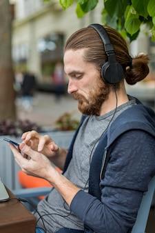 Zijaanzicht van de mens op een stadsterras met smartphone en hoofdtelefoon