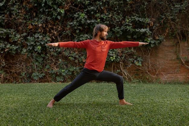 Zijaanzicht van de mens op het gras buiten doet yoga