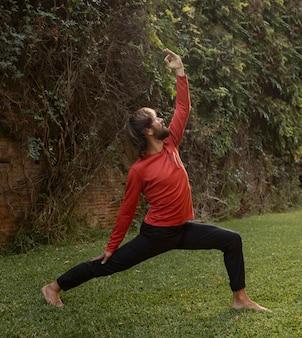 Zijaanzicht van de mens op het gras die yoga doet