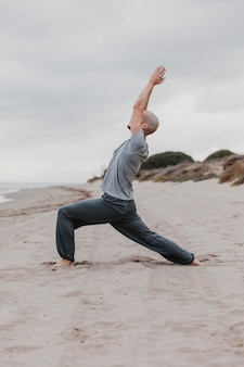 Zijaanzicht van de mens op het strand die yoga beoefent
