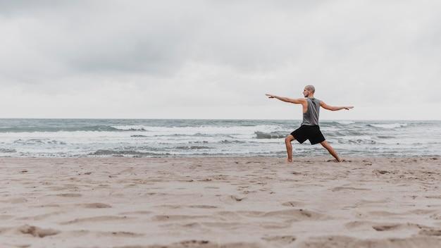 Zijaanzicht van de mens op het strand die yoga met exemplaarruimte uitoefenen