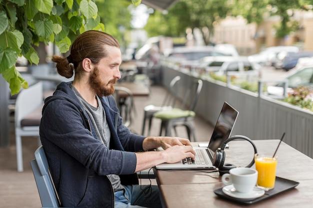 Zijaanzicht van de mens op terras dat aan laptop werkt