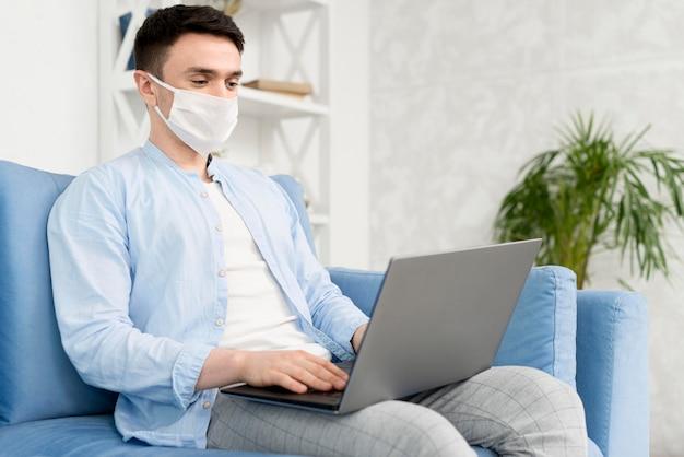 Zijaanzicht van de mens thuis met medisch masker dat aan laptop werkt
