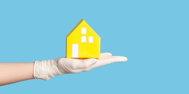 Zijaanzicht van de menselijke hand in witte chirurgische handschoenen die de buitenkant van het gele papieren huis in de hand houden.