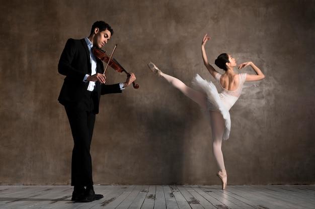 Zijaanzicht van de muzikant met viool en dansende ballerina