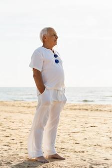 Zijaanzicht van de oudere man die met zonnebril de zon bewondert op het strand