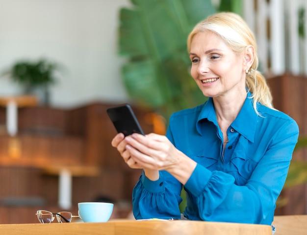 Zijaanzicht van de oudere smartphone van de vrouwenholding tijdens het werken