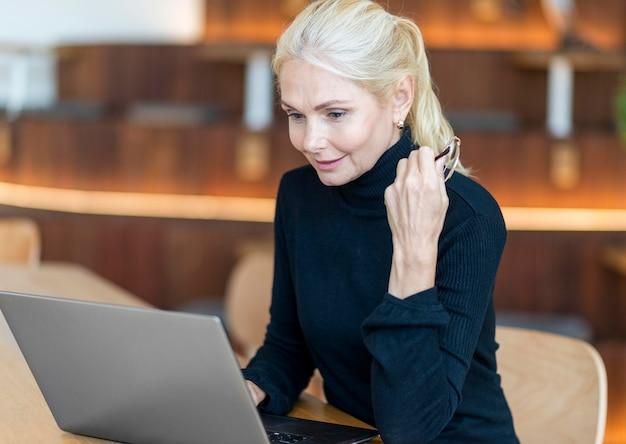 Zijaanzicht van de oudere vrouw met een bril die op laptop werkt