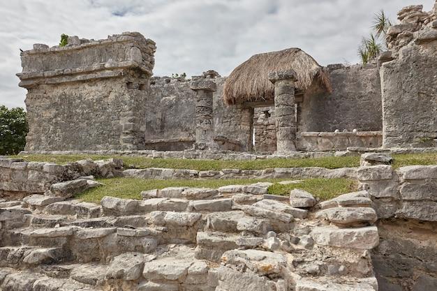 Zijaanzicht van de overblijfselen van een kleine maya-tempel in het tulum-complex in mexico, genomen bij zonsondergang.