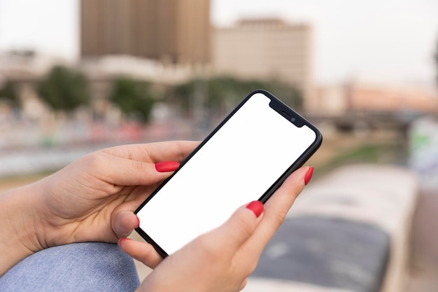 Zijaanzicht van de smartphone van de vrouwenholding terwijl buitenshuis