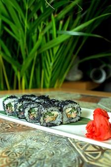 Zijaanzicht van de traditionele japanse broodjes van keuken zwarte sushi met de avocado van het krabvlees en roomkaas op groen
