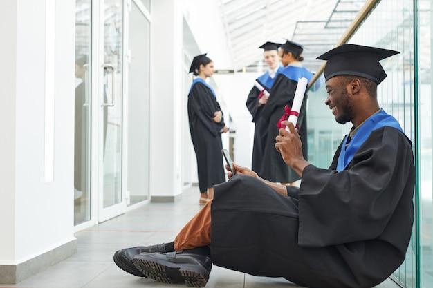 Zijaanzicht van de volledige lengte bij een gelukkige afro-amerikaanse man die een afstudeerjurk draagt met diploma naar videochat terwijl hij op de vloer zit, kopieer ruimte