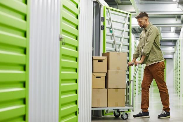 Zijaanzicht van de volledige lengte op knappe bebaarde man laden kar met kartonnen dozen in self storage unit, kopieer ruimte