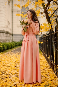 Zijaanzicht van de volledige lengte van een mooie sensuele jonge brunette bruid in roze trouwjurk en permanent in herfst park in de buurt van vintage kathedraal en bruiloft boeket, verticale foto te houden