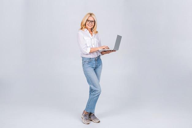 Zijaanzicht van de volledige lengte van lachen vrolijke oudere volwassen senior blonde vrouw dame 40s 50s staande werken op laptop pc-computer geïsoleerd op een witte grijze achtergrond.