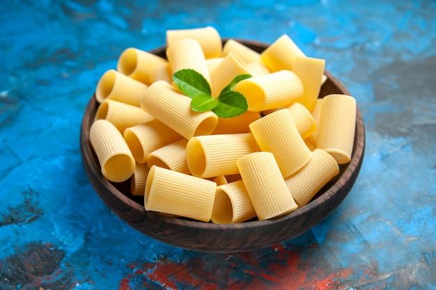 Zijaanzicht van de voorbereiding van het diner met pasta noedels met groen in een bruine pot op blauwe achtergrond