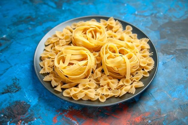 Zijaanzicht van de voorbereiding van het diner met pasta noedels op een zwarte plaat aan de linkerkant op blauwe achtergrond